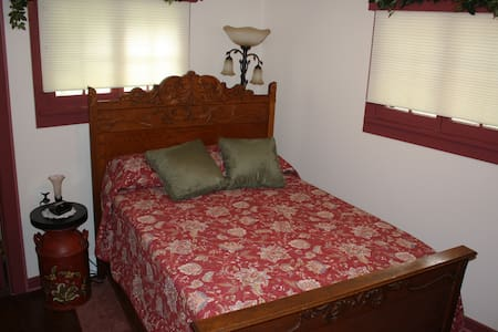 The bedroom is furnished with a lovely antique bedroom set and garden-themed decor.  There's TV, WiFi, and a small refrigerator in the room.