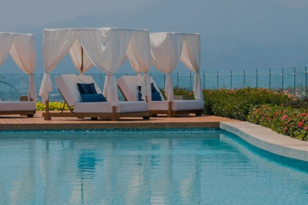 Enjoy a canopied padded lounge chair poolside.