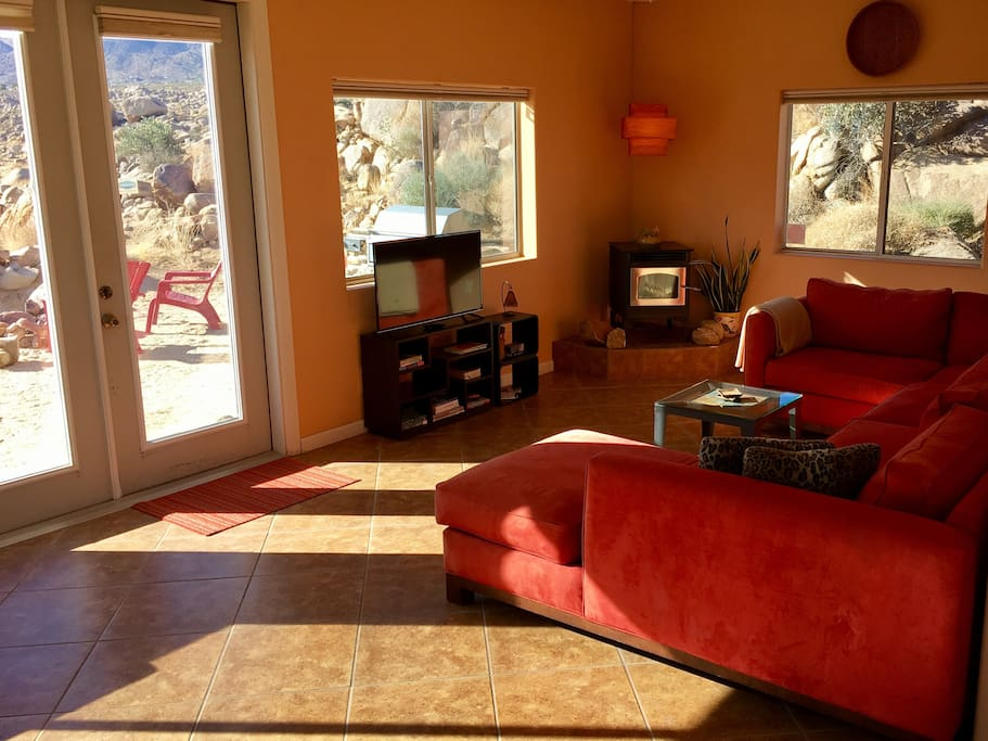 Living room with over-sized sofa, Smart TV, wood pellet fireplace and views of Coyote Hole Canyon.