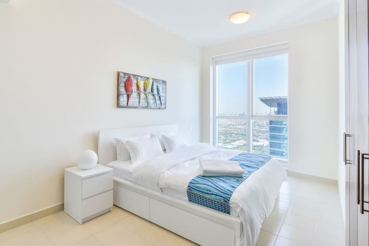 Art decorated master bedroom features a super comfy King size bed with sparking clean premium linen and bird's-eye views from floor-to-ceiling windows