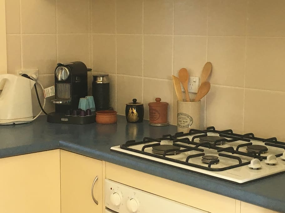 Kitchen with coffee machine, gas hot plates and electric oven