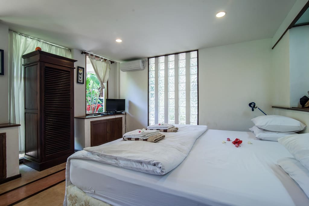 Bedroom with tv and cupboard.