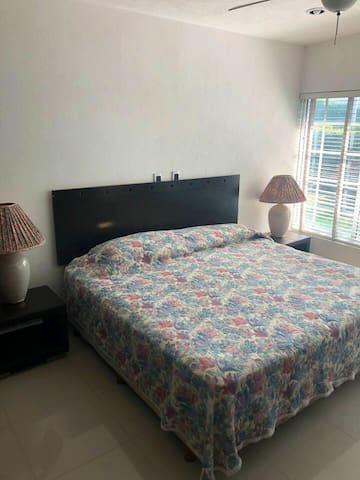 Recámara principal con cama kingsize, closet, baño privado, aire acondicionado y vista al jardín