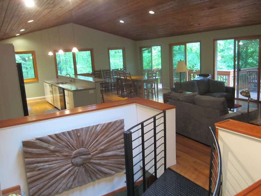 Open concept great room with kitchen, dining room, living room with fireplace, and spacious decks