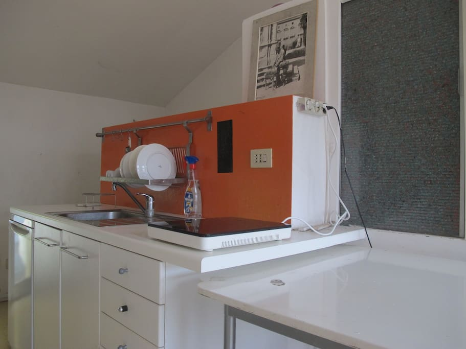 Kitchen with dishes, little frigo, microwave.