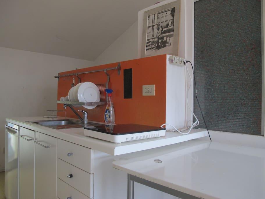 Kitchen with dishes, little frigo, microwave.