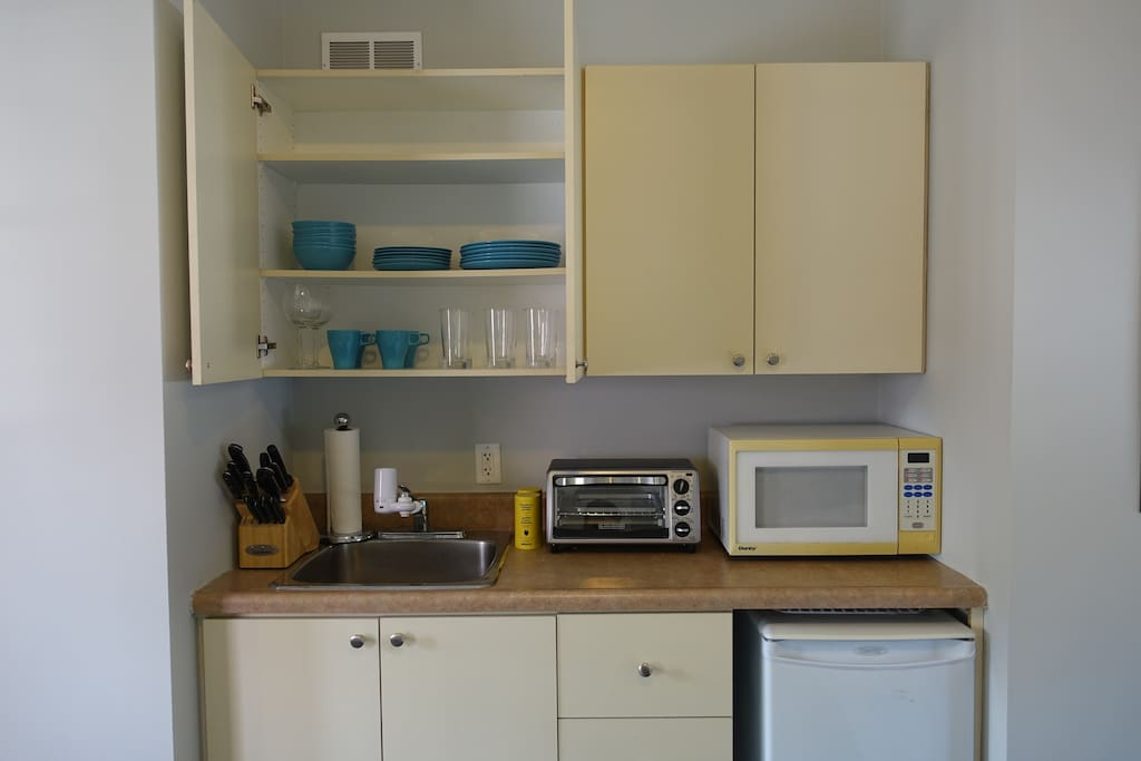 Kitchenette with toaster oven, microwave, Keurig coffee machine and bar fridge.