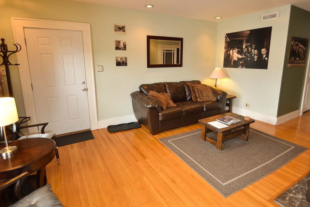 """Spacious living room with quality wood furniture, a leather couch and internet connected 48"""" TV."""