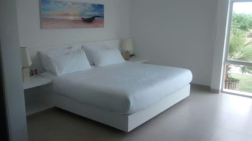 Habitación principal con cama king y baño privado, completamente dotado con sabanas, toallas y colchas.