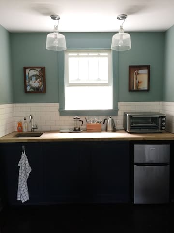The kitchenette comes equipped with a small refrigerator, toaster oven, electric kettle, french press, freshly ground coffee, tea options, glassware, plates/bowls, and wine opener.