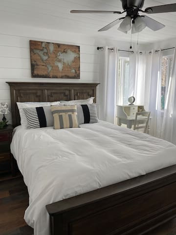 The bedroom facing the back and side of the home features a queen size bed, and has lovely afternoon sun. This bedroom also features a small writing desk that doubles as a vanity.