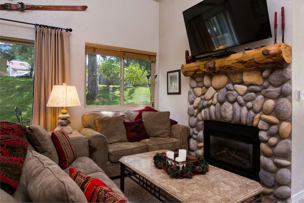Gather 'round the stone fireplace with flatscreen TV above