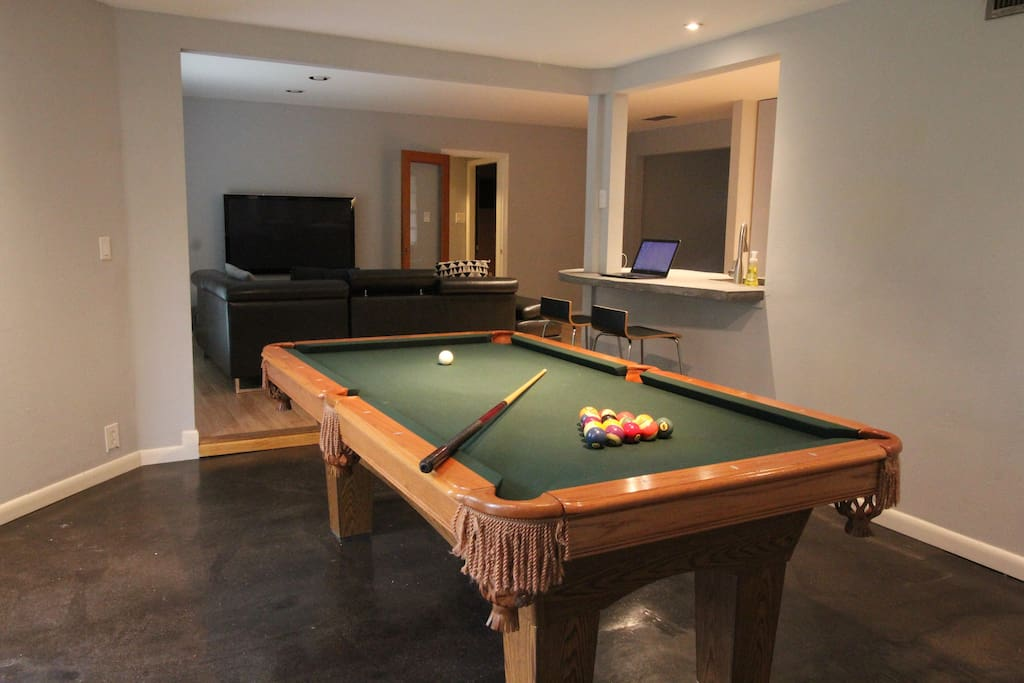 Custom pool table over looking the large screen television and laptop workspace/bar top.