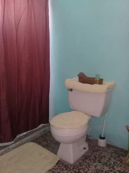 Cuarto de baño dentro de la habitación con ducha que tiene calentador de agua eléctrico. El baño no tiene puerta.