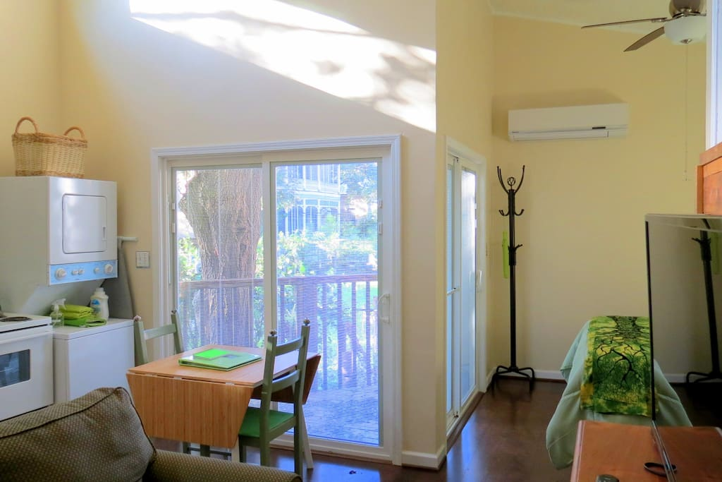 View from bathroom door looking toward main living area. Two sets of sliding doors open to the TreeHugger deck.