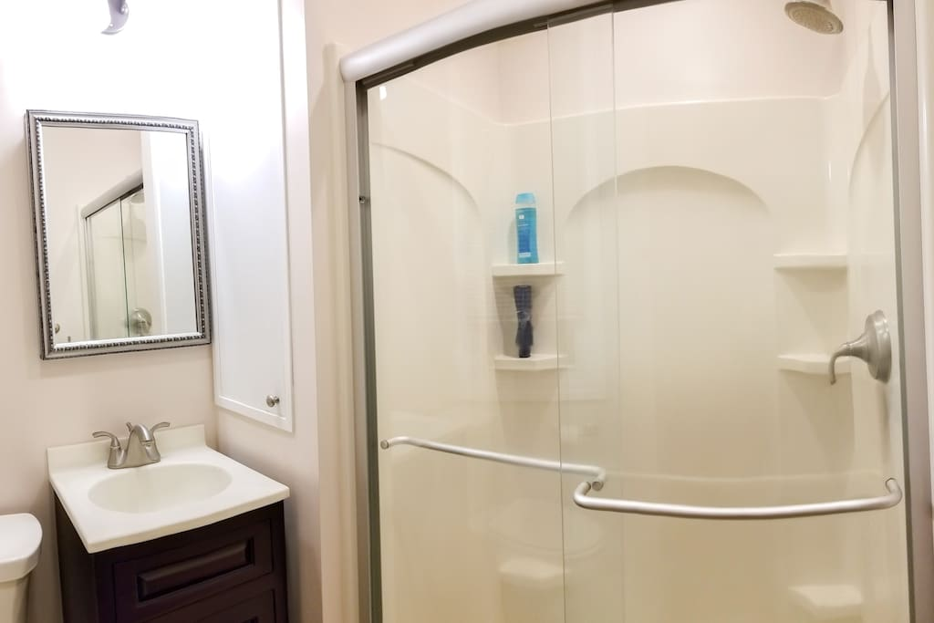 Stylish contemporary bathroom with glass-enclosed shower, and chrome and satin nickel accents