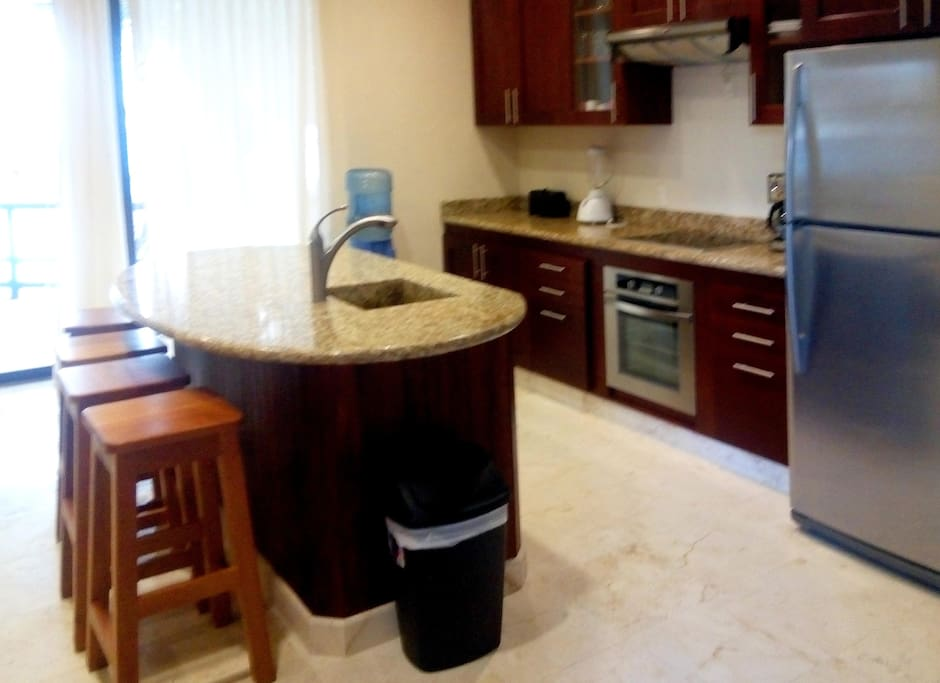 Fully equipped kitchen with microwave, full sized fridge and island bar.