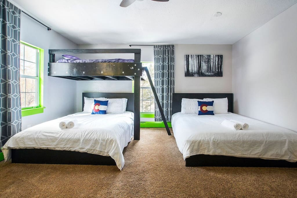 The green private room has 2 queen beds and one twin with a private bathroom