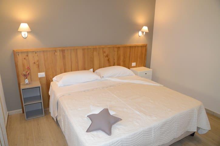 Camera matrimoniale con letti King-size. Testata e panca di legno di cedro.