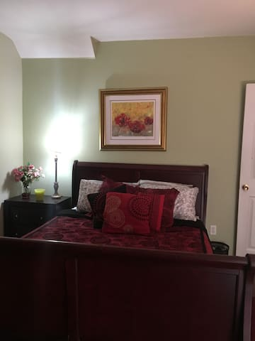 The master bedroom has a comfortable queen size bed, television, large closet, and additional storage in clothes cabinet.
