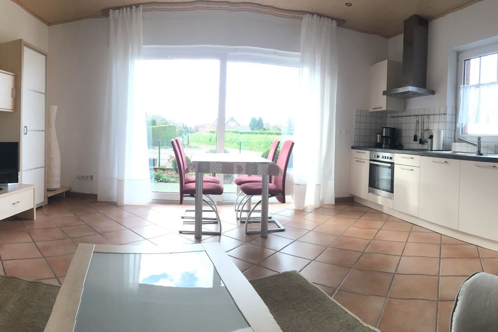 Wohnküche - Aussicht vom Sofa ins Grüne, Tisch mit 4 Stühlen, Küchenzeile