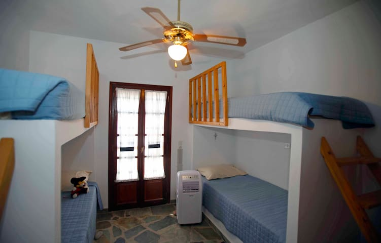 Second bedroom with four bunk beds and air conditioning. the double doors lead to a balcony shared with the master bedroom.