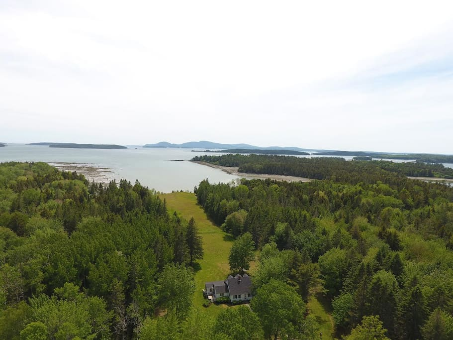 View of the house, yard, field, meadow, cove, bay, Mt. Desert Island and Cadillac Mountain.