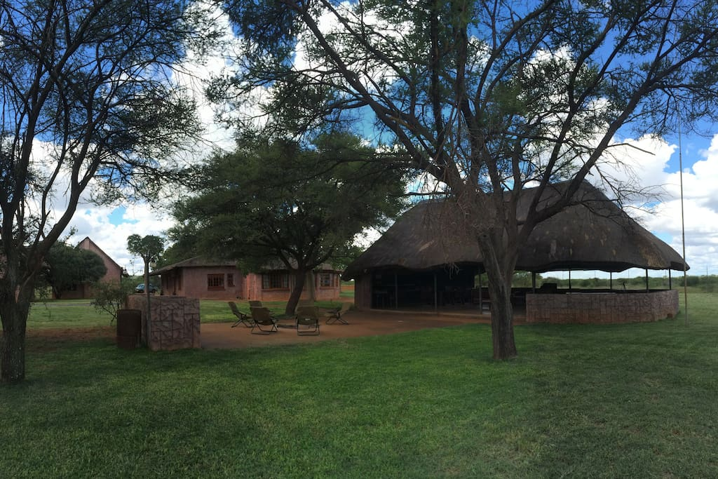 Thatched roof entertainment area overlooking a waterhole in front of the lodge