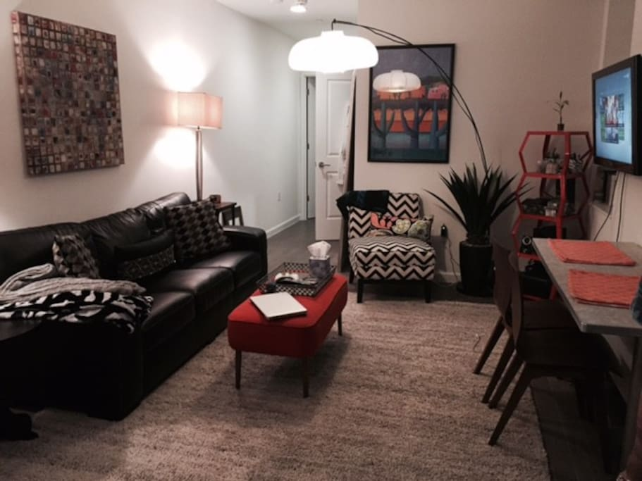 Large living room with TV, comfy couch, funky decorations and a full-sized dining room table.