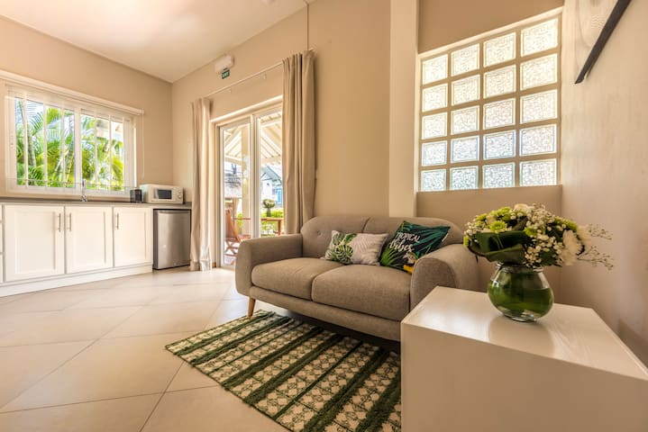 Small living area with Kitchen overlooking the terrace and garden with shared pool