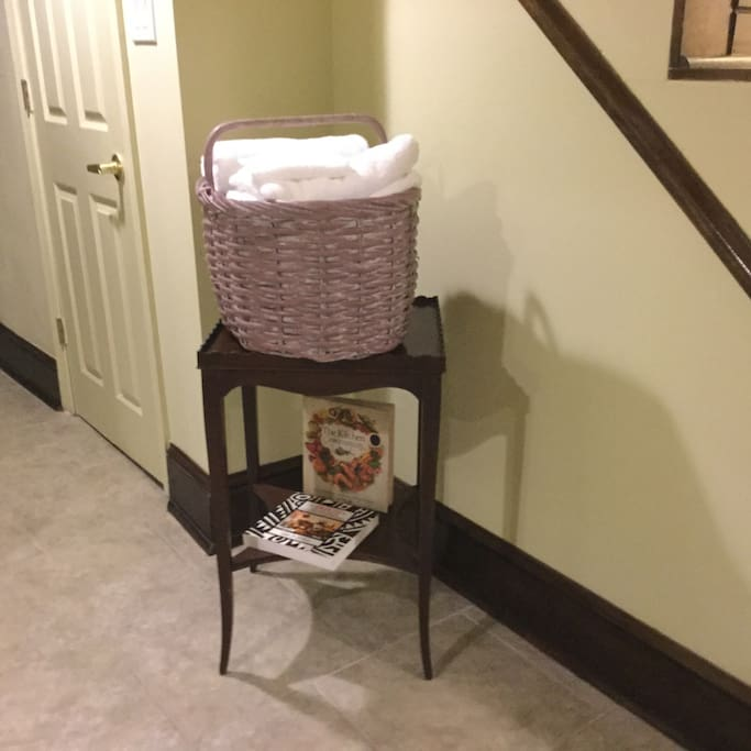Cherry wood stand holding a basket of fresh towels and washcloths