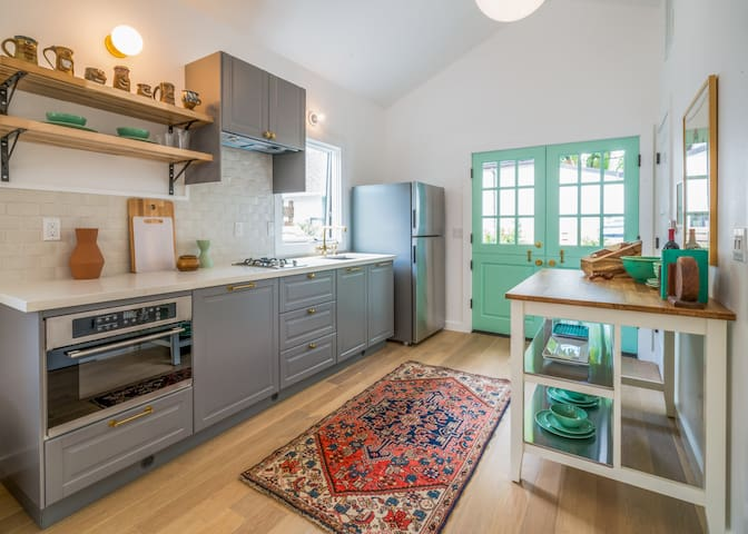 Open kitchen with a garden view.  Opens to outdoor dining area.  High ceilings with natural light.  Every detail in mind to make you feel like you are at home away from home.
