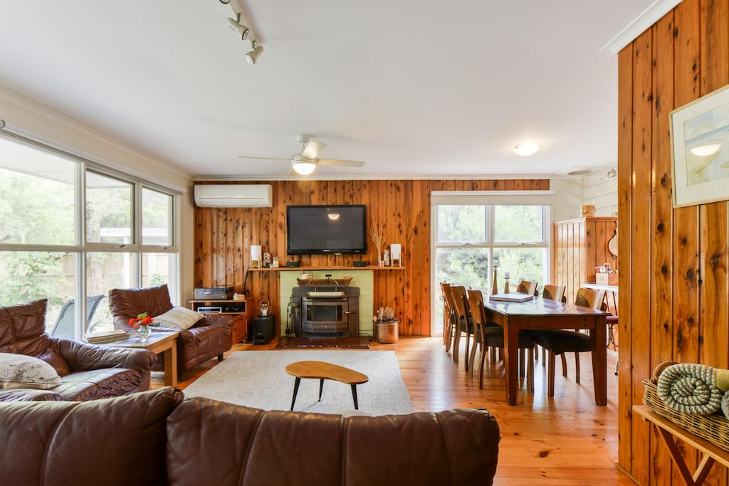 Enjoy the fireplace, AC and heating split system, large TV, record player, bose speakers, cupboard full of DVDs, DVD player, and large dining table, all in an open plan, light filled rom.