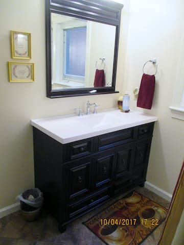 Bathroom vanity, window with peekaboo view of lake seen in mirror.  Clean towels are stored inside this unit.  Please put your used towels in the laundry basket provided when you go, also add your sheets after you strip the bed.