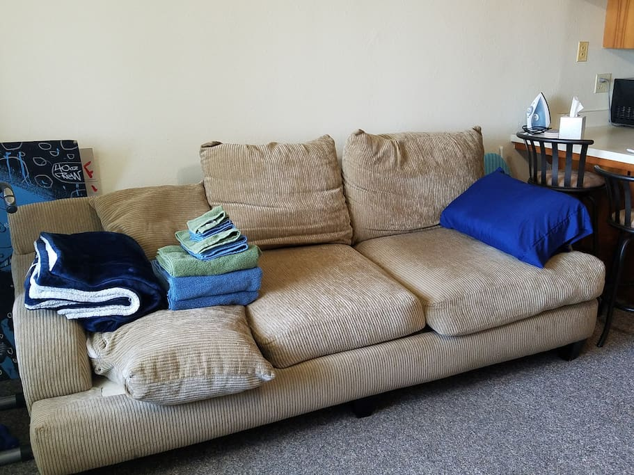 Plush corduroy sofa with pillow and soft blanket