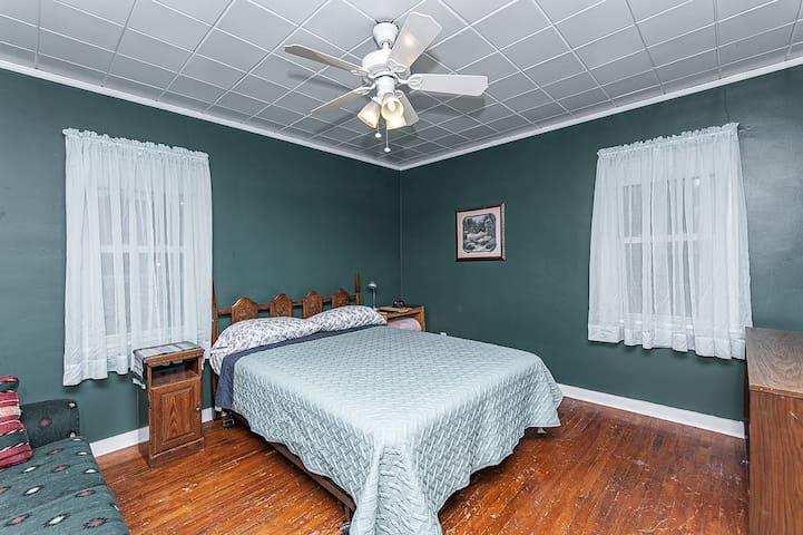 Main bedroom with queen bed, dresser, sofa, closet
