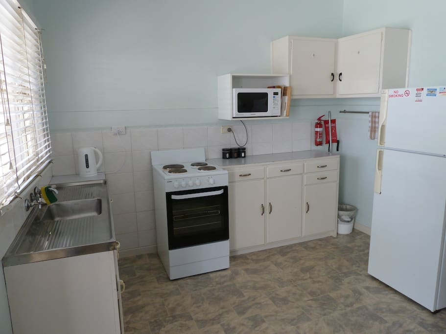 Full kitchen with fridge freezer microwave stove oven and cooking accessories.