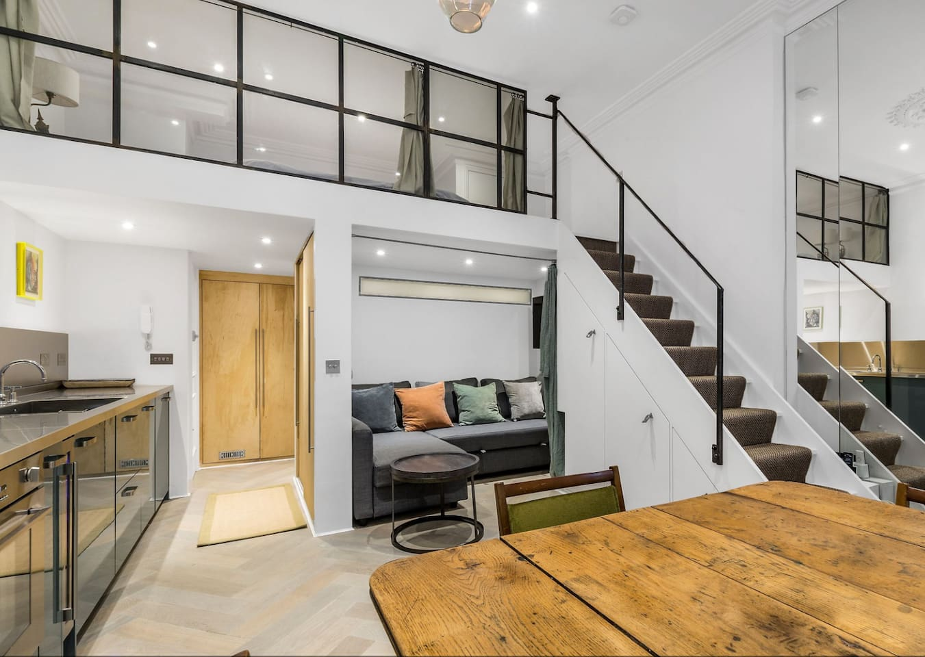 Studio overview image showing the galley kitchen, TV zone, stairs leading to the enclosed sleeping area