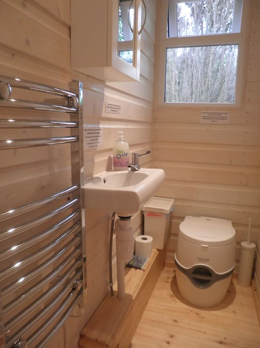 toilet area with heated towel rail, hand basin and portable loo.