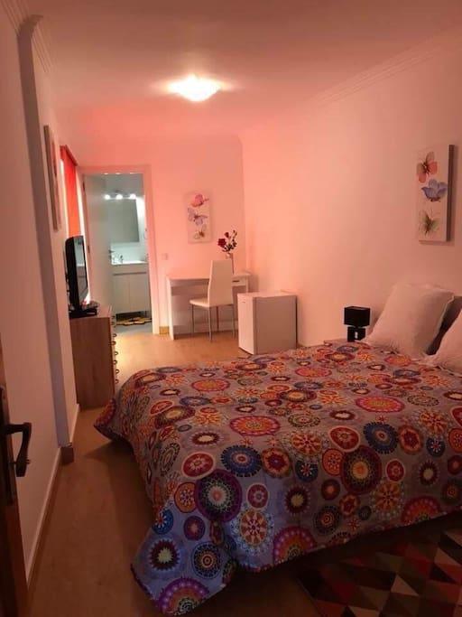 Interior mostrando a tv,cama de casal,frigobar e mesinha com cadeira.