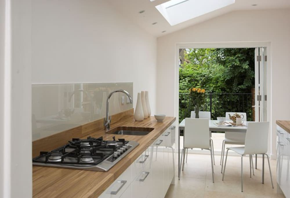 Kitchen with bifold doors opening on to small private garden