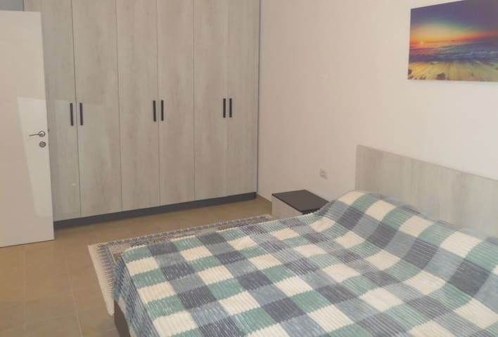 Queen size bed. The space behind the door has an iron board, electric iron, vacuum cleaner. There are extra pillows, sheets, and covers inside the dresser.