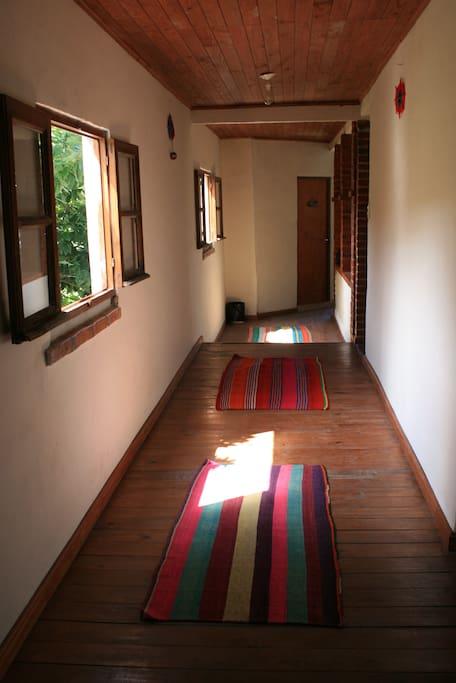 El pasillo a las habitaciones, y el verde de la ventana que quiere entrar por todos lados