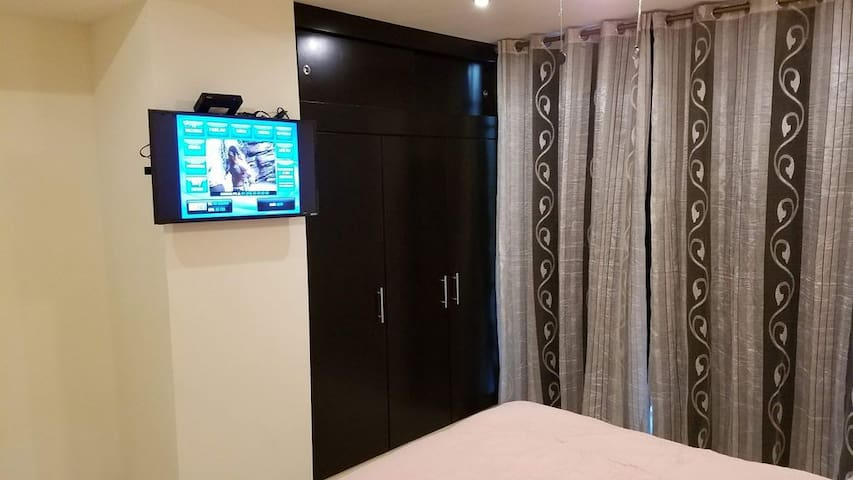 Master bedroom  with flat screen TV and closet space