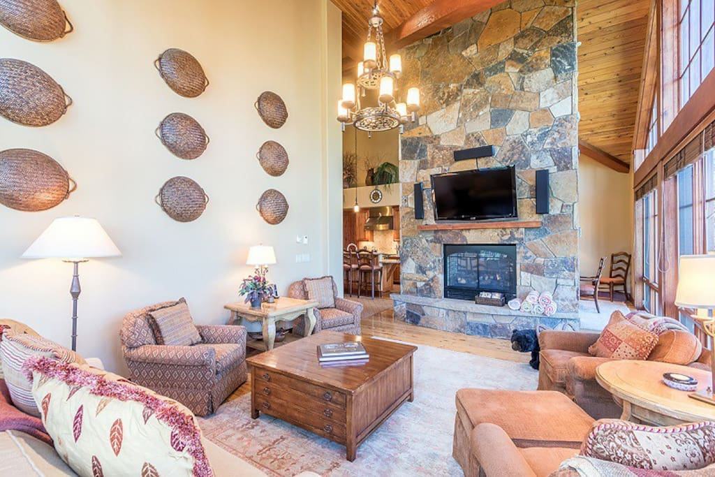 Large stone fireplace in living area, flat screen TV above mantle