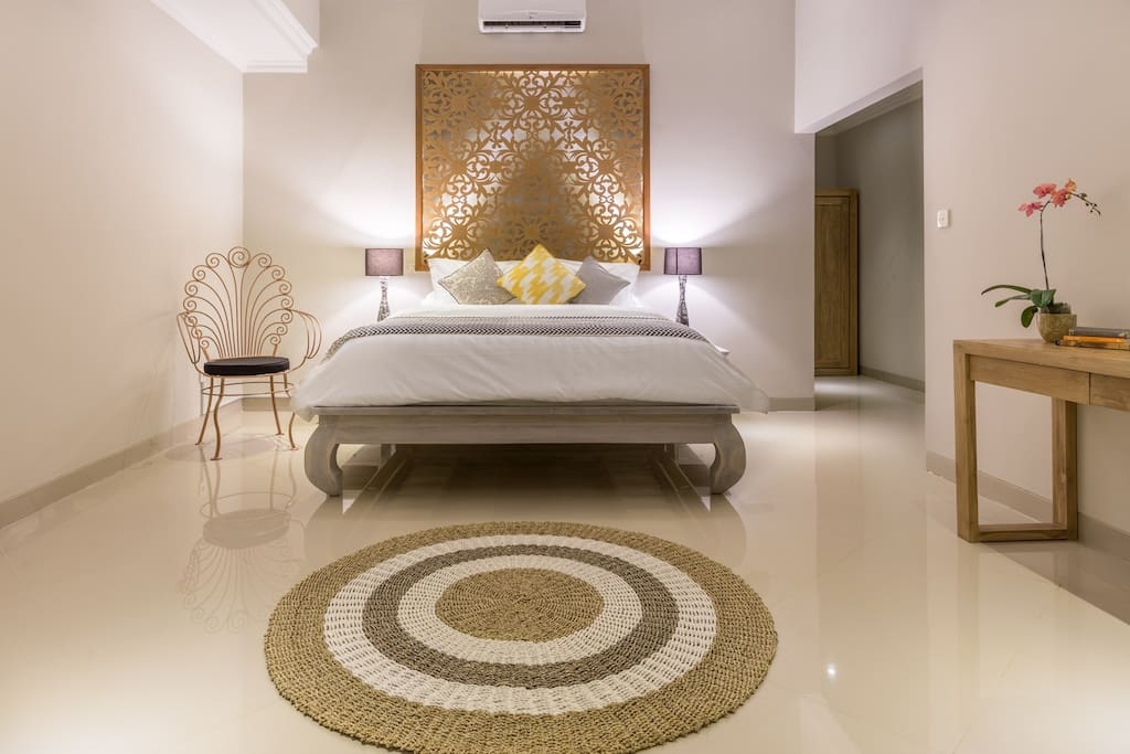 The First Grand Master bedroom boasts a blend of Balinese teak and modern furniture with a backlit headboard designed and hand carved exclusively for Gratitude Villa.  Generously sized with high ceilings, all bedrooms contain full block out curtains for optimal jet lag recovery and extra privacy.