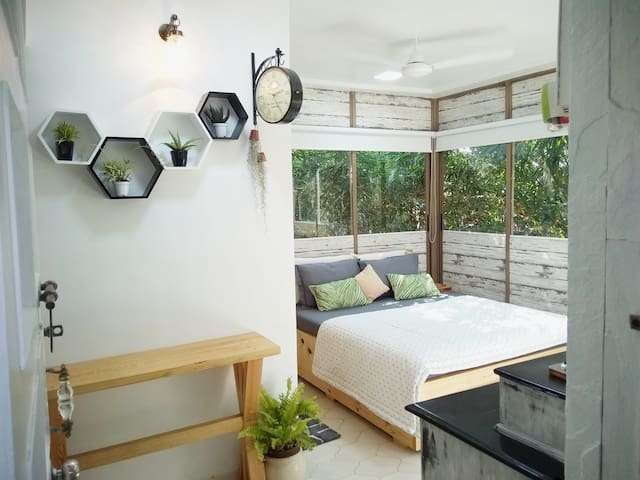 Clean bed with two memory foam and two regular pillows. A backdrop of tall trees. Attached bath / rest room. Easy roller blinds with blackout screens for convenience and privacy when needed