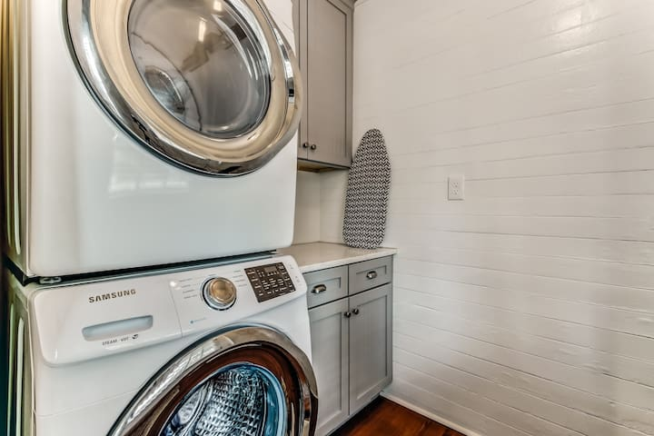 Modern washer, dryer, laundry supplies, iron, and ironing board all available for your convenience.
