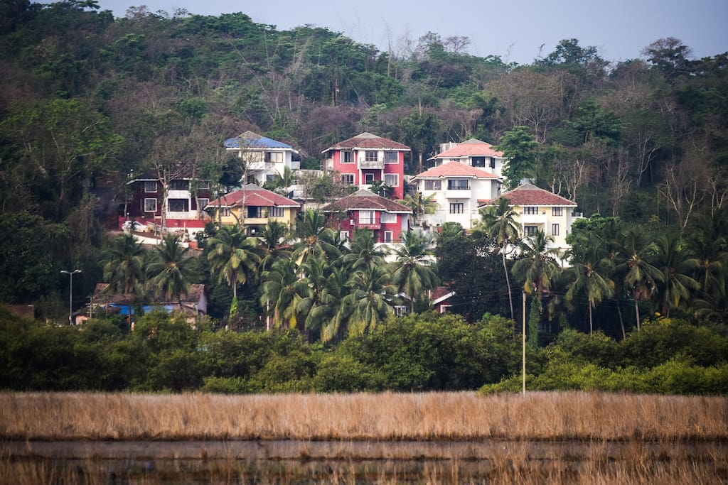 Nestled on a hillside in a small gated community surrounded by lush woodland overlooking the backwaters of the Mandovi