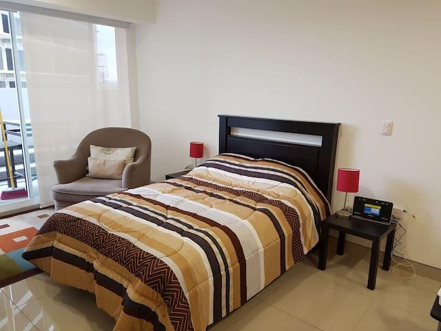 Recámara equipada con cama matrimonial y cómodo sofá